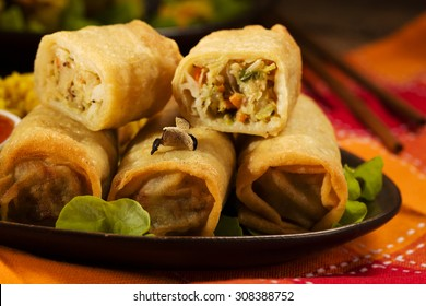 Portion baked spring rolls with vegetables and rice on a plate, served with sauce.