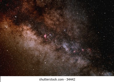 A portion of the central buldge of the Milky Way galaxy showing dense star fields and dark dust lanes.