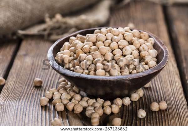 Portion of Chick Peas (close-up shot) on wooden background