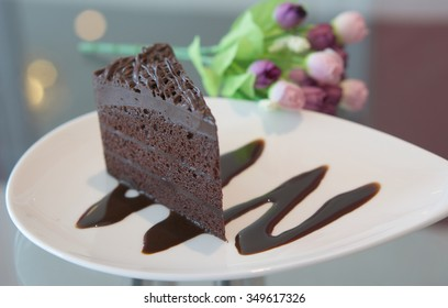 Portion of chocolate cake with  bouquet flower on mirror table.