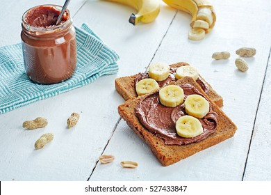 Portion of chocolate peanut butter sandwiches with rye bread and bananas over white background. Healthy breakfast with saturated fats.