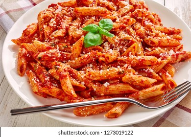 a portion of classic italian penne arrabiata with basil and freshly grated peccorino cheese on a white plate on an old wooden table, view from above, close-up. macro