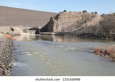 A portion of the Cochiti Dam on the Rio Grande River in central New Mexico, with water flowing from the spillway and into the riverbed