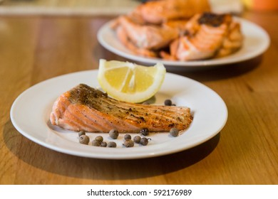 Portion of cooked salmon fillet with lemon slice on white plate with fork and knife on wooden table