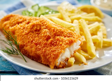 Portion of crispy breaded fish fillet with french fries served on plate
