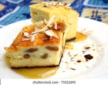 portion of curd pie with raisin, honey and almond on white plate