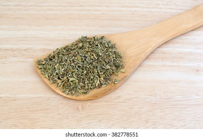 A portion of damiana leaf on a spoon atop a wood counter top.