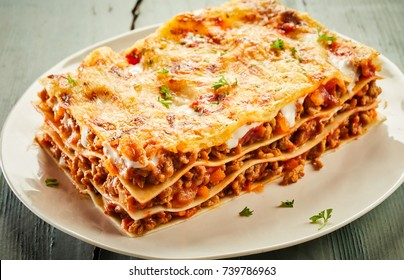 Portion of delicious cheesy beef lasagne served on a plate showing the layers of noodles, meat and mozzarella cheese suitable for advertising in a menu