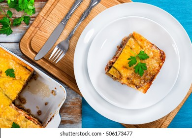 portion of delicious moussaka decorated with parsley cooked for authentic recipe, on plates and in gratin on white peeling paint  boards, view from above