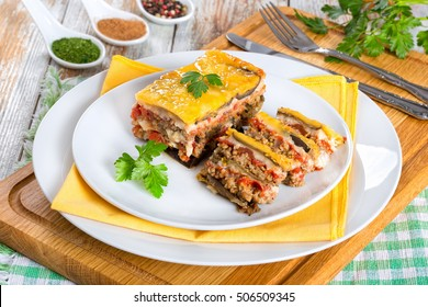 portion of delicious moussaka decorated with parsley cooked for authentic recipe, on plates, on white peeling paint  boards, view from above