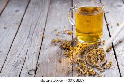 Portion of dried Camomile (close-up shot) on an old wooden table