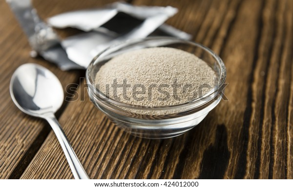 Portion of dried Yeast (close-up shot) on wooden background