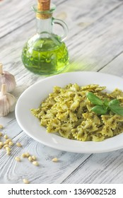 Portion of farfalle with pesto with ingredients on the white wooden table