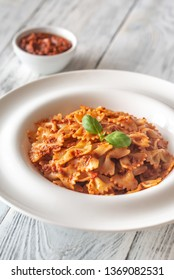 Portion of farfalle with sun-dried tomato pesto on the white wooden table