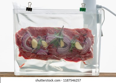 Portion of flat iron beef steak sous-vide cooking suspended in a clear plastic bag in hot water with a spirg of fresh rosemary and onions to flavor