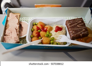 Portion of food for one passenger in cardboard box at airplane board.