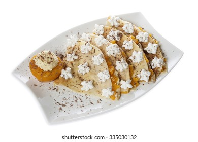 Portion of four pancakes stuffed with vanilla cream and peach, decorated with whipped cream and grated chocolate, served on a white plate. Isolated on white.