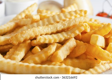 Portion of French fries (Crinkle-cut) deep fried, close up.
