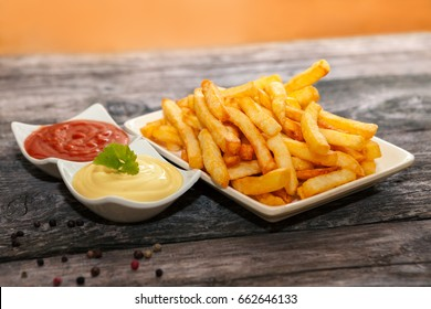 Portion of french fries with tomato sauce and mayonnaise