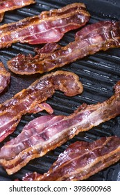 Portion of fried Bacon in a pan (close-up shot)