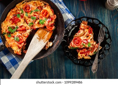 Portion of frittata with eggs, sausage chorizo, red pepper, green pepper, tomatoes, cheese and chili in a plate on wooden table. Italy cuisine. Top view.