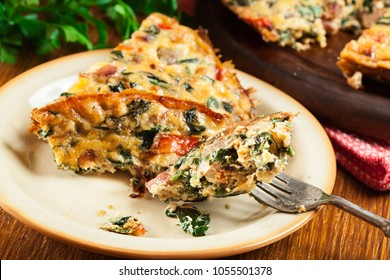 Portion of frittata made of eggs, mushrooms and spinach on a plate. Italian cuisine