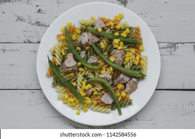 Portion of fusilli pasta with tuna, green beans and corn on white plate and gray wooden table. Healthy food
