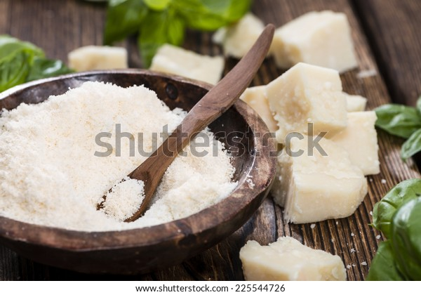 Portion of grated Parmesan Cheese on dark wooden background