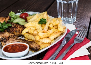 Portion of grilled Chicken Legs with Chips