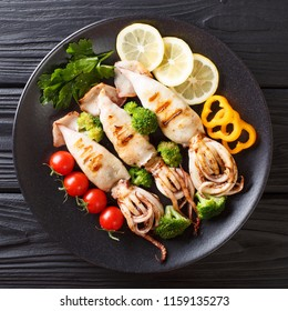 Portion of grilled squid with fresh vegetables close-up on a plate on a black table. top view from above
