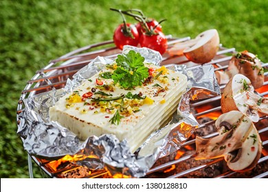 Portion of halloumi or tofu in aluminium foil grilling over the fire on a barbecue with fresh sliced mushrooms and tomatoes outdoors on green grass