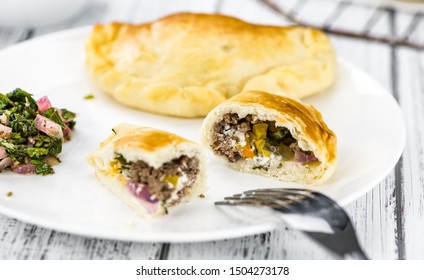Portion of healthy Empanadas on an old wooden table (selective focus; close-up shot)