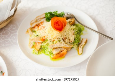 Portion of healthy salad made of leaves of fresh salad, cheese, slices of meat and tomato. Top of it decorated with rose made from fresh tomato.