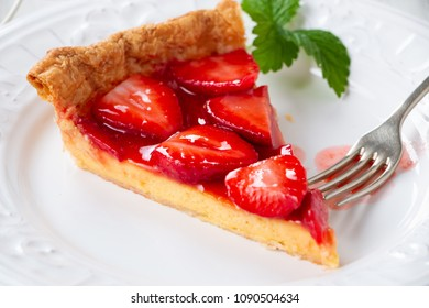Portion of homemade pastry strawberry tart on a white dish close up