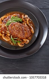 portion of hot savory juicy salisbury beef steaks with delicious mushroom onion gravy served on black plates on wooden table, vertical view from above