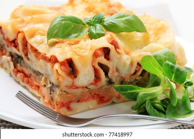 Portion of lasagna garnished with salad greens