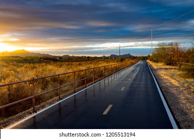 A portion of The Loop walking, biking, running and jogging path in Tucson, Arizona. A beautiful Sonoran Desert Sunset lights up the sky and the roadway wet with recent rain reflects the railing. 2018.