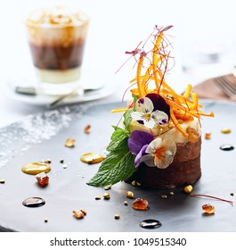 Portion of luscious sweet chocolate cake and coffee. Close up of delicious fresh dessert decorated with Myosotis pretty flowers on a plate. Beautiful decoration, restaurant dish, ready to eat.