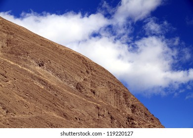 A portion of a mountain and a blue sky in the background