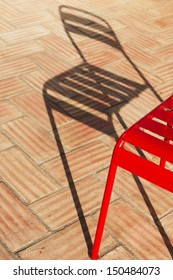 A portion of an old retro metal chair with a long shadow
