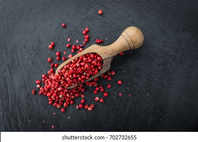 Portion of Pink Peppercorns as detailed close up shot on a slate slab; selective focus