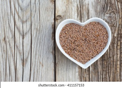 Portion of Psyllium Seeds on rustic wooden background. Natural light. Selective focus.