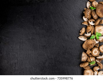 Portion of Raw Shiitake mushrooms on a rustic slate slab, selective focus, close-up shot