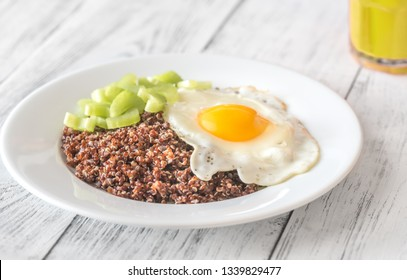 Portion of red quinoa with fried egg and celery on the wooden table