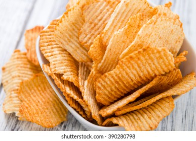 Portion of rippled Potato Chips (selective focus) on an old wooden table