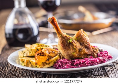 Portion of roast duck leg red cabbage homemade dumplings on plate and red wine on the background.