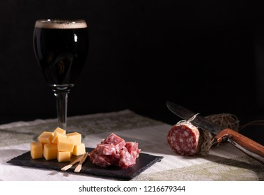 portion of salami and cheese with a dark trappist beer in selective lighting