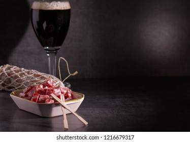 portion of salami with a dark trappist beer in selective lighting
