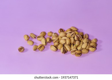 Portion of salted open pistachios on a plain lilac background