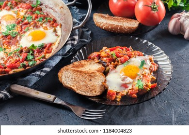 Portion of shakshuka on a plate. Middle eastern traditional dish with fried eggs, tomatoes, bell pepper, vegetables and herbs.